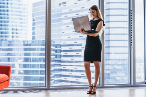 commercial windows woman standing by office window