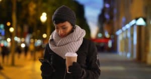 woman wearing scarf using smart thermostat app on her phone