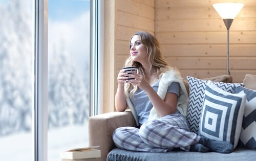 woman sat in warm house looking outside through the window